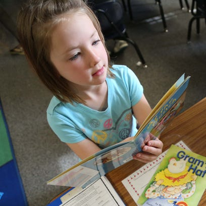 Nora Wright, 5, reads a book in Micaela Tuttle's kindergarten
