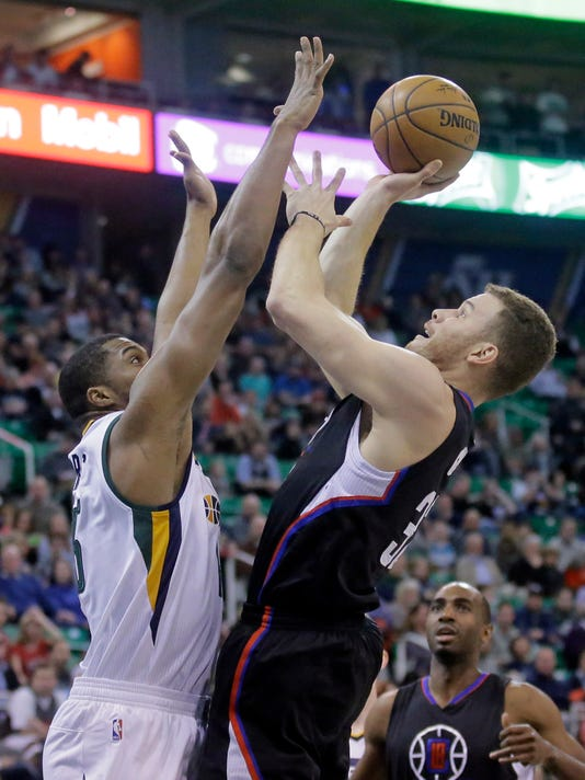 Los Angeles forward Blake Griffin, right, shoots as Utah Jazz forward Derrick Favors, left, defends in the first half during an NBA basketball game Monday, Feb. 13, 2017, in Salt Lake City. (AP Photo/Rick Bowmer)