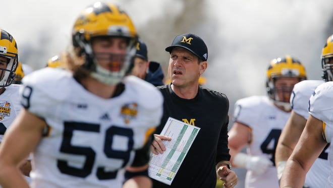 Michigan coach Jim Harbaugh, center, is not backing down in the fight over whether the Wolverines should hold part of their spring football practice in the SEC's backyard.