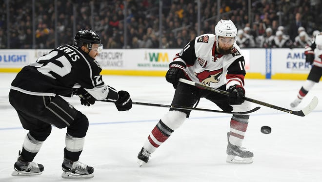 Arizona Coyotes center Martin Hanzal, right, of the Czech Republic, passes the puck as Los Angeles Kings center Trevor Lewis defends during the first period of an NHL hockey game, Thursday, Feb. 16, 2017, in Los Angeles.