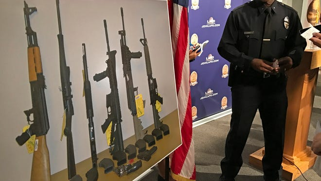 Los Angeles Police Department Cmdr. Horace Frank, right, shows a photo of multiple weapons found in the Agoura Hills home of a man charged with making terrorist threats to the Islamic Center of Southern California, during a police news conference Tuesday in Los Angeles. Mark Lucian Feigin was arrested last week on the charge.