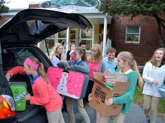 Students in the Southern Delaware School of the Arts' National Junior Honor Society pack suitcases with everyday items for guests of the HALO shelter in Salisbury.
