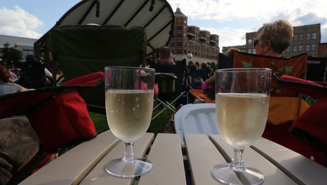 Two glasses of wine sit on a portable table between a couple at the concert on The 400 Block, June 17, 2015.
