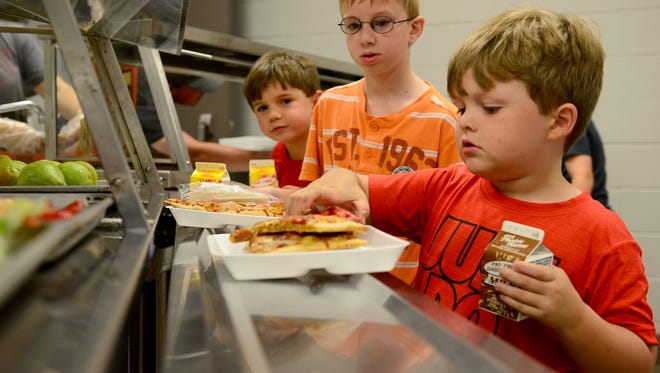 Tucker Hopkins, Caleb Gordon, and Remington Buckley wait in line to get their fruit and salad during the Seamless Summer Meals Program at Trenton Elementary School, Thursday, June 1.