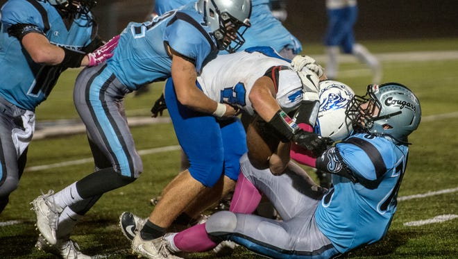 Lansing Catholic's Ian Moore, right, and Evan Zarotney, left, tackle Ionia's James Paulin during the third quarter on Friday, Oct. 6, 2017, at Cougar Stadium in Lansing.
