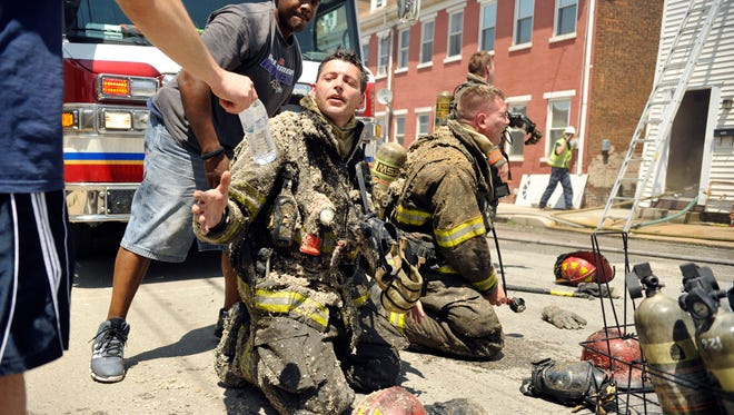 York City firefighter Ivan Flanscha receives a bottle of water as his oxygen tank valve is relieved after he and Brandon Hyder, center right, emerged from a three-alarm fire at Girard Avenue and Prospect Street in May 2013.