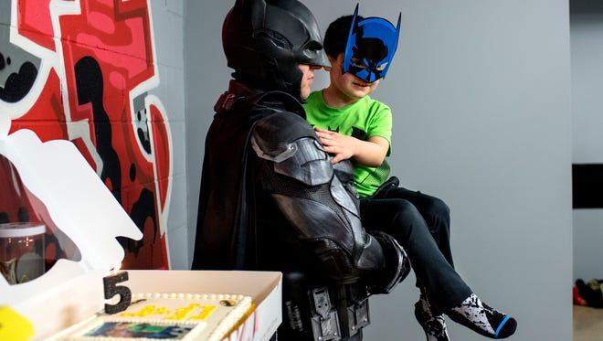 Shamus Smith, dressed as Lansing Batman, left, holds 5-year-old Vincent Gentile while guests sing him happy birthday during his birthday party on Saturday, March 24, 2018, at the District5 Extreme Air Sports trampoline park in Lansing. Members of the League of Enchantment dressed as superheroes and attended the boy's birthday party. He is recovering from retinoblastoma, a rare eye cancer.