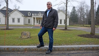 """Retired Air Force Col. David Antoon is shown in front of the Hunting Valley, Ohio police station and town hall where he was arrested in December for violating a protective order by posting a Yelp comment online. He fought his former urologist, Cleveland Clinic surgeon Jihad Kaouk, in court for nearly a decade. In December, the case involving a surgery that left him gravely injured, incontinent and impotent, became one about negative online comments and emails Antoon sent to Kaouk. It was settled July 11 with Antoon pleading to a """"minor misdemeanor"""" of disorderly conduct and agreeing to pay a fine of $100. This eight month battle cost Antoon more than $40,000 in legal fees and other costs."""