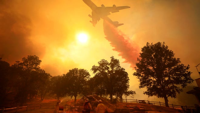 The Global SuperTanker, a 747 converted into a firefighting aircraft, drops flame retardant in front of advancing flames from a wildfire Thursday, Aug. 2, 2018, in Lakeport.