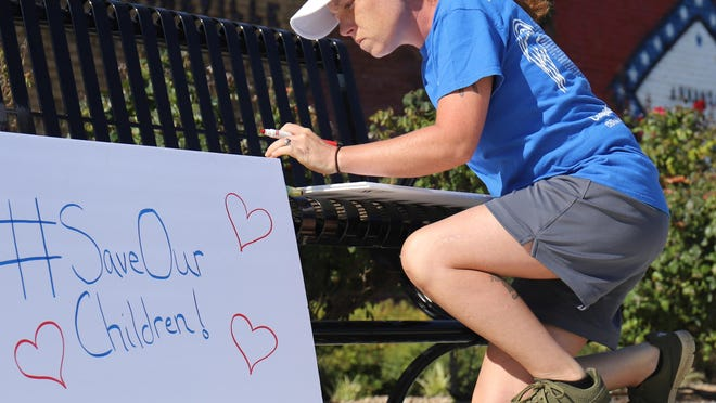 Chandra Harger makes posters for the Save Our Children Rally, Saturday, Aug. 22, 2020, joining others at the corner of Second and Broadway in downtown Booneville to bring attention to child trafficking in the United States.