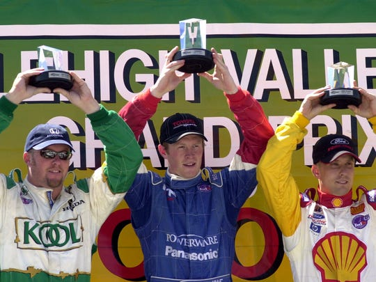 From left, Paul Tracy of Canada, Scott Dixon of New Zealand and Kenny Brack of Sweden hold up their trophies on the podium after the Lehigh Valley Grand Prix at the Nazareth Speedway in Nazareth, Pa., May 6, 2001. Dixon won the race.