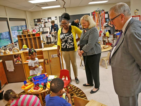 Pre-k assistant Nikkia Owens, left, talks with Sarah
