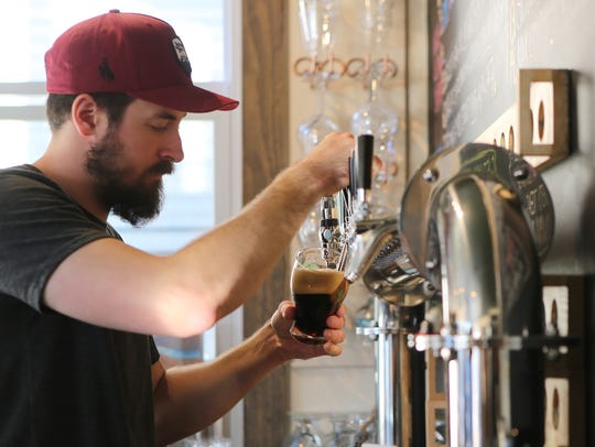 Bartender Scott Ruel draws a beer from the tap at Seven