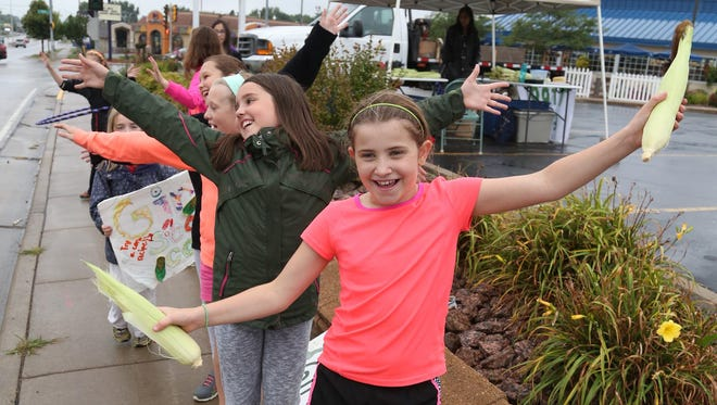 Holding two ears of corn, Cameron Gluege, 10, Marshfield, and sister scouts from Troop 6181 finish a song and dance number as they sell sweet corn at the corner of N. Central and Upham St. in Marshfield, Friday. Directly behind Gluege is Jacolyn Kloos, 9, of Stratford.