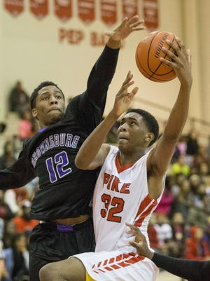 Tahjai Teague of Pike High School, puts up a shot as Michael Fowlkes of Brownsburg High School goes for the block during boys basketball at Pike High School, Indianapolis, Saturday, Jan. 3, 2015.
