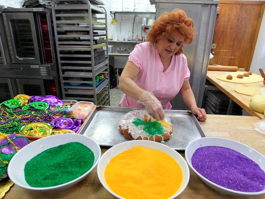 Aggie Purcell, owner of Aggie's Bakery & Cake Shop decorates a King's Cake to sell as part of a Mardi Gras tradition.