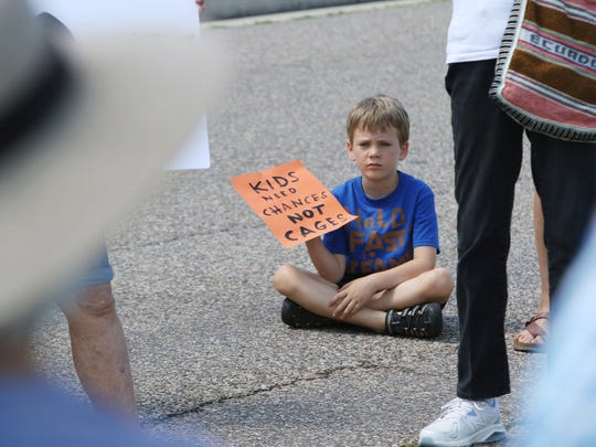 Abel Bergland, 6, of Staunton attends a rally with his family at the Shenandoah Valley Juvenile Center in Verona on Saturday, June 23, 2018.  The crowd carried signs in opposition to the alleged abuse to immigrant teens held at the detention center as well as other national issues.