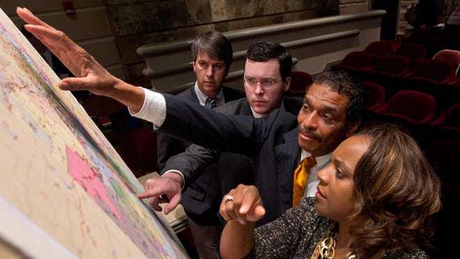 Alabama lawmakers examine a map of the redistricting plan at the Statehouse in 2012.