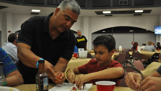 Albert Ornelas shows 9-year-old Raynee Chester how to crack open crawfish at the first Crawfish Boil Monday, April 2, 2018.