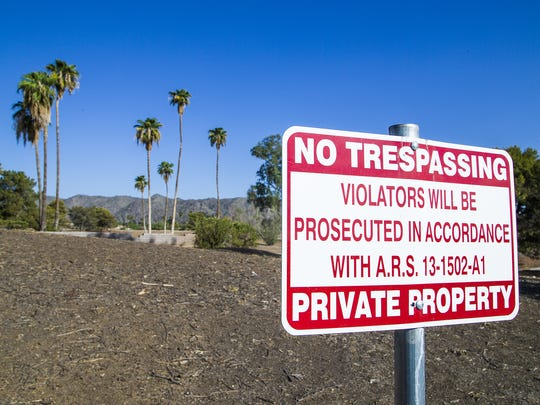 A sign stands on the edge of the closed Ahwatukee Lakes