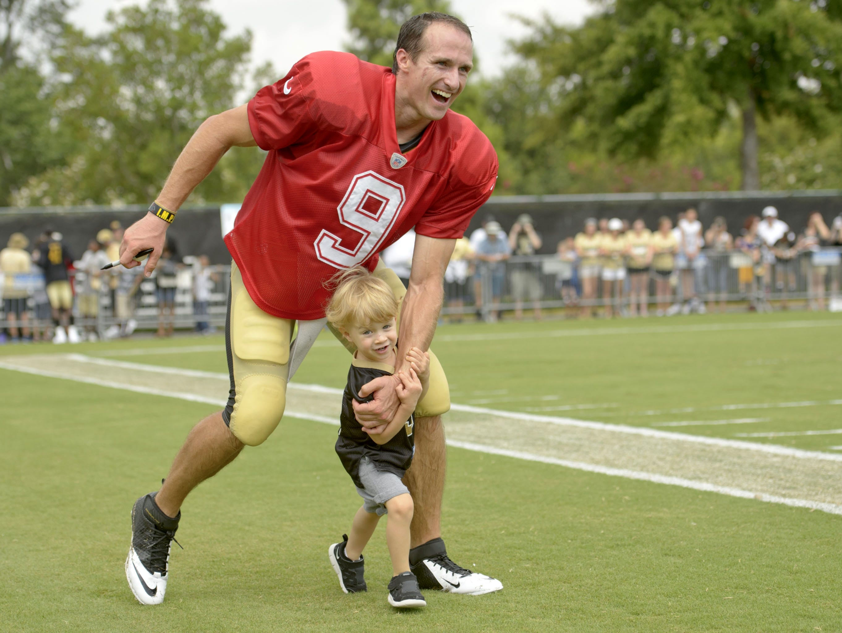 New Orleans Saints quarterback Drew Brees (9) plays with his son Bowen during training camp.