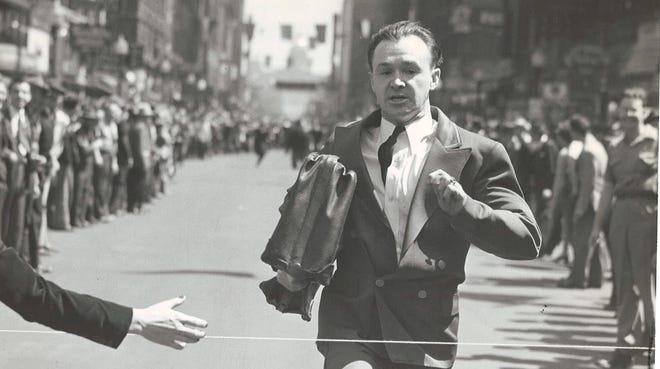 1942: Ray Kelsey hits the tape first on Locust Street before a huge crowd in Des Moines during Drake Relays week in the Bellboys' relay race.