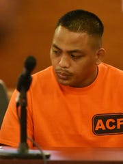 In this January 2015 file photo, Ray Tedtaotao Camacho averts his eyes as his victim, Monique Baza, takes the stand to ask for a maximum sentence at the Superior Court of Guam.