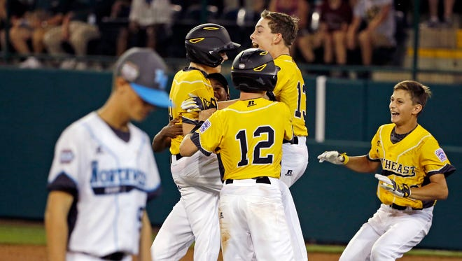 Bend, Ore.'s Zack Reynolds, left, walks off the field as Goodlettsville's Robert Carroll, left center, celebrates his two-run walk-off double in the bottom of the sixth inning of a baseball game in U.S. pool play at the Little League World Series baseball tournament in South Williamsport, Pa., Thursday, Aug. 18, 2016.