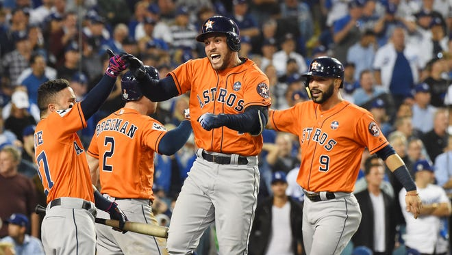 Astros players, from left to right, Jose Altuve, Alex Bregman, George Springer and Marwin Gonzalez celebrate Springer's two-run home run against the Dodgers in the second inning of Game 7 of the 2017 World Series at Dodger Stadium in Los Angeles.