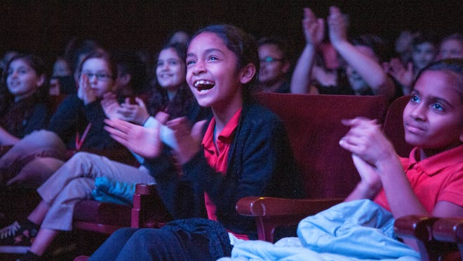 Jaslynn Gonzalez, center, a 4th grader at John H. Winslow Elementary School, applauds as members of all-vocal rock band Face, from Boulder, Colorado, hold a musical workshop for Vineland students prior to performing a concert for the students at the Landis Theater in Vineland on Friday morning.