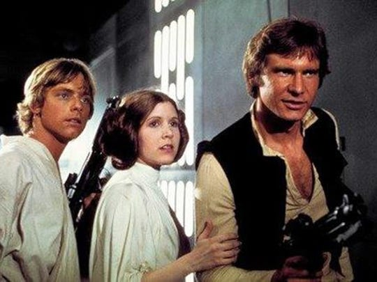 """Mark Hamill, left, as Luke Skywalker, Carrie Fisher as Princess Leia Organa, and Harrison Ford as Hans Solo in the original """"Star Wars."""""""