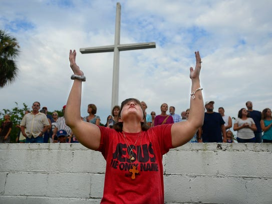 Heidi Belanger prays on Sunday, June 25, 2017, during
