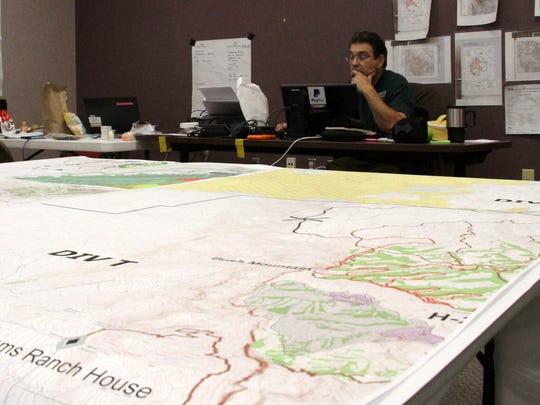 Team members worked to predict where the fire will move next at the Incident Command Post on Monday.