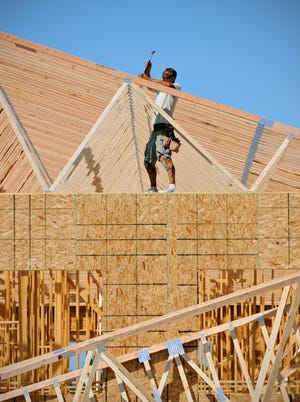 Carpenters place trusses onto an addition to the existing STRIDE Academy Middle School building July 23.