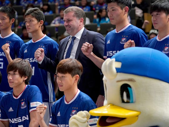 Yokohama F Marinos new head coach Ange Postecoglou of Australia poses with new players during a press conference in Yokohama, near Tokyo, Sunday, Jan. 14, 2018.  Former Australia coach Postecoglou was introduced as head coach of the J-League's Yokohama F. Marinos on Sunday. (AP Photo/Shizuo Kambayashi)