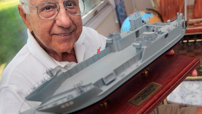 D-Day veteran Joseph Alexander, 91, a native of Indianapolis who also lives part time in Fort Myers Beach, Fla., holds a model of LCT 856 that he was skipper of as a young Navy ensign on D-Day during World War II. Alexander had a crew of 16 and another officer (who was killed) that landed at Omaha Beach on June 6, 1944, under heavy fire just two hours after the first wave of landings.