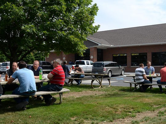 Holden's customers enjoy a picnic-style lunch on benches set up outside the store Friday.