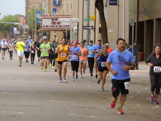 Runners make their way north on Cypress Street, past the Paramount Theatre during the Mayor's Race 2016, in downtown Abilene.