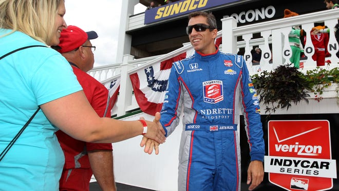 Verizon IndyCar Series driver Justin Wilson (right) shakes hands with a fan prior to the ABC Supply 500 at Pocono Raceway.