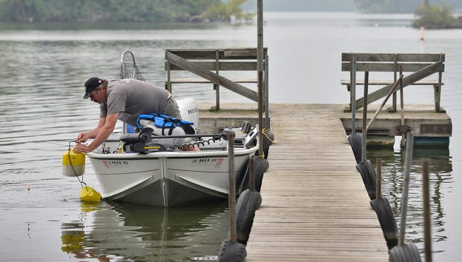 Brian Schaefer, Rowley, Iowa, reaches for his live bait bucket as he fishes for crappies from a dock Tuesday at Ruegemer's Island View Resort on Horseshoe Lake near Richmond. The Sauk River Chain of Lakes is much cleaner than it was 50 years ago and may get cleaner due to new Minnesota Pollution Control Agency standards.