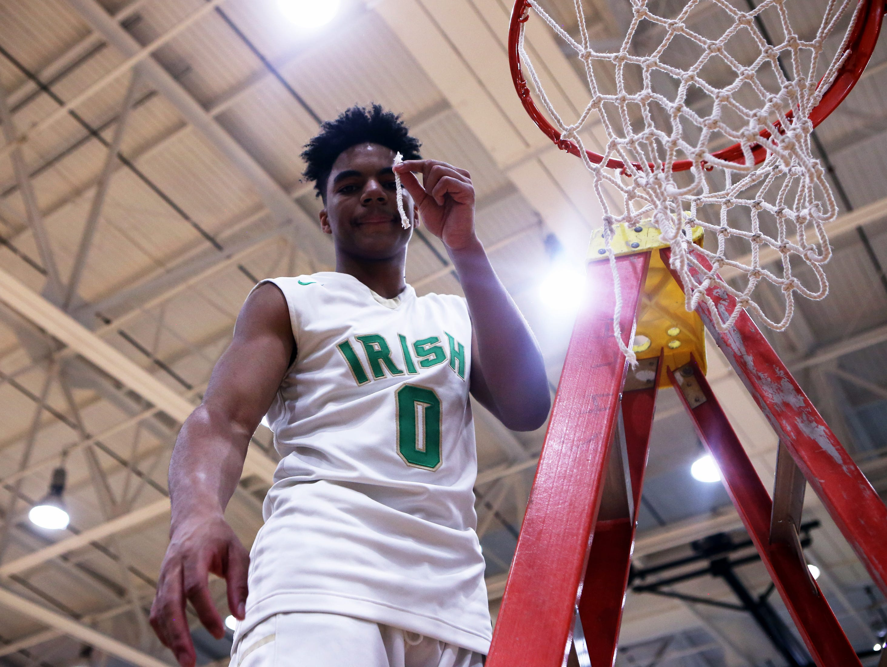Cathedral's James Franklin cuts a piece of net following the Irish's City tournament win.