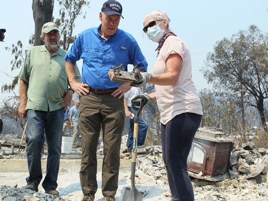Secretary of the Interior, Ryan Zinke, listens to Patti Peters who's helping her brother to salvage the house which destroyed by the Carr Fire in the Keswick township on Sunday morning. Patti found a book stopper in the debris of the house and shows it to Sec. Zinke.