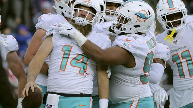 Miami Dolphins quarterback Ryan Fitzpatrick, left, celebrates his touchdown run with teammates against the New England Patriots on Dec. 29 in Foxborough, Mass. Fitzpatrick led the undermanned Dolphins to five wins this season.