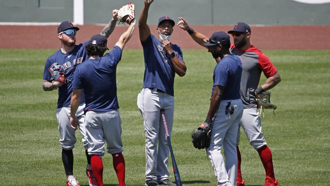 Red Sox coach Tom Goodwin, center, celebrates with players after a recent workout at Fenway Park.