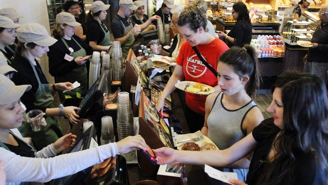 Customers pay for their orders as Panera Bread holds a preview event to benefit Second Harvest Food Bank Monday, March 16, 2015, at the restaurant's new location on Johnston Street in Lafayette, La. The store is slated to officially open this Saturday.