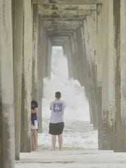 Scott Crawford snaps a photo of waves under pier after
