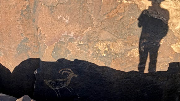 Reporter Brian Passey's shadow appears above a petroglyph