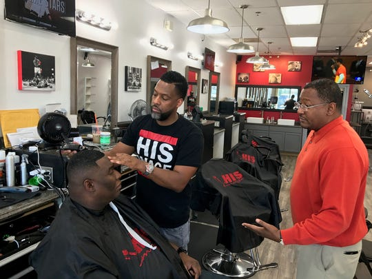 Frank Hawkins (right) talks to Ivan Thomas and Derrick Reed about his work with AIDS Delaware. The organization works with local barbershops to get the word out about HIV prevention.