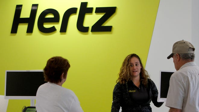 Assistant Branch Manager Madelyn DeMasi, center, helps Ann and William Caldwell with their rental car Wednesday at the new Hertz car sales/rentals building, which opened its doors Dec. 1. in Estero.