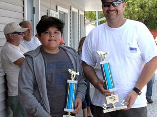 Northeastern Wisconsin Great Lakes Sport Fishermen hosted their 39th Annual Kids' Fish Derby for Bigs and Littles in the Big Brothers Big Sisters mentoring program Aug. 5. Biggest fish of the day trophy went to Little Brother Cruz on the Slippery Clam boat with Captain Glen Kappelman. From left to right in the photo are Little Brother Cruz and Captain Glen Kappelman. Captain Glen Kappelman also won the Largest Catch Trophy for bringing in the largest catch of six fish with a total weight of 54.41 pounds.